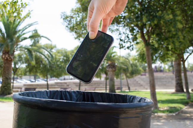 Man throwing a phone in the trash